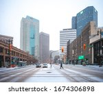 Small photo of Winnipeg, Manitoba/Canada - March 2020: A person crossing Portage Avenue during a light snowfall