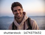 Small photo of Young good-looking chap is smiling with a gorgeous sunset view