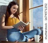 Young girl sitting on window...