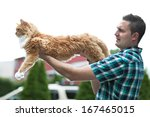 Small photo of Man holding his cherished purebred Maine Coon cat outright to show his size. Shallow depth of field.