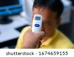 Body Temperature Measurement. Female Doctor Checking Temperature Using Infrared Thermometer - stock photo
