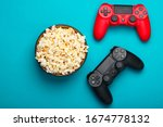 Two gamepads and a bowl of popcorn on blue background. Gaming, leisure and entertainment concept. Top view