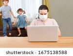 Home office. Working from home vs. Mom wearing medical face  Work with two kids on the Internet on a laptop at home. quarantine. Corona Virus.  - stock photo