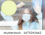 Small photo of portrait of a red-haired girl behind glass in a protective face mask as a concept of quarantine and isolation due to covid-19 coronavirus, border closure and social disunity, empty frame, copy space