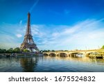 Small photo of Paris Eiffel Tower reflecting in river Seine with bridge Pont d'Iena in Paris, France. Eiffel Tower is one of the most iconic landmarks of Paris., toned