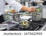 Small photo of Professional chef workplace at cuisine of restaurant. Close up view of man hand stirring soup with spoon. Cooking, catering, culinary, gastronomy and food concept