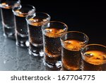 Small photo of Glasses with an alcoholic drink on a damp glass table