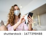 Small photo of European woman in face mask cleaning the phone by hand sanitizer, using cotton wool with alcohol to wipe to avoid contaminating with Corona virus. Cleaning mobile phone to eliminate germs, Covid-19.