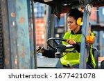 Female Worker Driving Forklift...