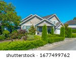 Small photo of Big custom made luxury house with nicely landscaped and trimmed front yard and driveway to garage.