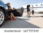 Small photo of wealthy woman stepping out of car parked in front of private plane and airhostess