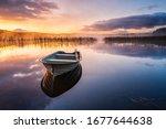 Boat On Still Lake At Sunrise ...