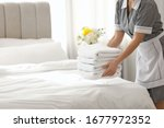 Young Chambermaid Putting Stac...