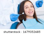 Small photo of Closeup male hands in gloves are holding dental tools. Smiling young woman is sitting in chair in clinic, office. Man doctor, orthodontist is conducting examination, treating teeth. Visit to dentist.