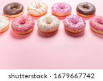 Small photo of Doughnuts with multicolored glaze laid out in two rows on trendy pink background. Doughnuts are traditional sweet pastries. Copy space for text.