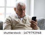 Old Man Sit On Sofa Hold...
