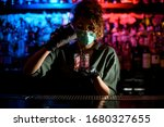 Small photo of Young barman girl in medical mask and black gloves professionally pour drink from steel glass into glasse with ice. Blue and red warning lights in background inform about coronavirus quarantine.