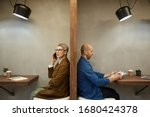 Small photo of Minimal side view portrait of two adult people separated by wall while sitting in separate cafe booths, copy space