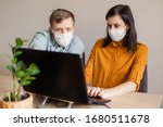 Small photo of A young family works from home at the computer. Quarantined couple coronavirus in medical masks. The call to stay home safe. Order food products online. Laptop freelancer dispute business office