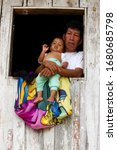 Small photo of father and son at their shack window in ecuadorian amazonia love room family group lodge life community protection hut wood small senior commitment baby window shack size tiny youth son care living re