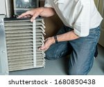 Small photo of Senior caucasian man changing a folded dirty air filter in the HVAC furnace system in basement of home