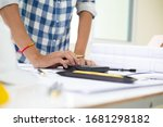 Small photo of hand Architect calculating budge Construction project with blueprint at Construction Site.concept