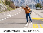 Small photo of Travel woman hitchhiking. Beautiful young female hitchhiker by the road during vacation trip in mountains Montenegro
