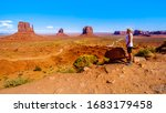 Woman enjoying the view of the sandstone formations of Mitten Buttes and Merrick Butte in Monument Valley Navajo Tribal Park in southern Utah, United States