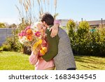 Small photo of Senior mother as a mother thanks her son for the bouquet for Mother's Day