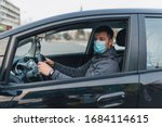 a man driving a car puts on a medical mask during an epidemic, a taxi driver in a mask, protection from the virus. Driver in black car. coronavirus, disease, infection, quarantine, covid-19 - stock photo