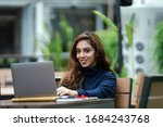 Small photo of Portrait of a young, attractive, confident, smart and studious Indian Asian smiling as she types and works on her laptop computer. She is sitting at a desk in her university, office or coworking space