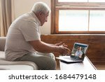 Small photo of Side view middle aged mature older man sitting on sofa, looking at computer screen, holding video call listening grown up handsome son, explaining how important stay at home during virus outbreak.