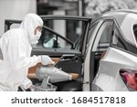 Small photo of Disinfectant worker character in protective mask and suit sprays bacterial or virus in a car.