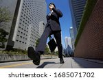 Small photo of A Japanese male businessman walks briskly through an office district.