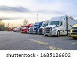 Small photo of Different big rigs semi trucks with semi trailers standing in row on truck stop parking lot with reserved spots for truck driver rest and compliance with established truck driving regulations