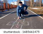 A Young Man Draws Hopscotch On...