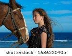 Girl With A Horse On The Beach