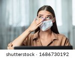 Small photo of Don't Touch Your Face. Girl wearing surgical mask rubbing her eye with dirty hands, working on laptop