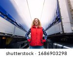 Portrait of female trucker proudly standing between trailers and truck vehicle. Transportation service. - stock photo