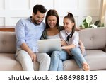 Small photo of Happy bearded man embracing smiling wife and adorable school aged girl, watching funny video on computer. Affectionate family of three playing game on laptop or shopping online in internet store.