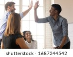 Small photo of In boardroom gathered businesspeople diverse guys buddies greets giving high five express amity. Team members multi-ethnic leaders congratulate each other with common success, respect gesture concept