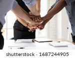 Small photo of Close up diverse businesspeople stacked their palms together showing support amity and loyalty. Concept of business team unity, common project, start important negotiations mate encouraging each other