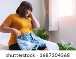 Small photo of Oversize young woman want to wear short jeans. Overweight female sitting on the bed holding pants jeans worried about weight gain. Plus size model girl with cellulitis.Obesity and weight loss concept.
