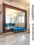 Huge mirror with wooden frame and turquoise pouf - stock photo
