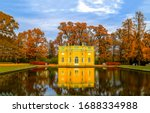 Autumn park pond landscape. Yellow house at park pond water. Russian autumn park pond. Autumn pond house view