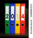 Four color binders with New Year 2014 digits placed on bookshelf - stock photo