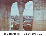 Cityscape of Budapest, Hungary photographed through the arch window of the Fishermans Bastion. Hungarian Parliament Building, Orszaghaz, in the far background on the other side of the Danube river.