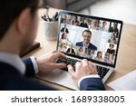 Small photo of Rear view of businessman speak on web conference with diverse colleagues using laptop Webcam, male employee talk on video call with multiracial coworkers have online meeting briefing from home