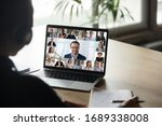 Small photo of Back view of female employee engaged in team Webcam conference on laptop, have online briefing or consultation from home, woman worker speak talk on group video call with diverse colleagues