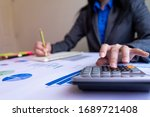 Small photo of Close up woman hand using calculator and writing make note with calculate about cost at office.